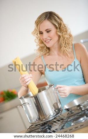 woman cooking pasta indoors - stock photo