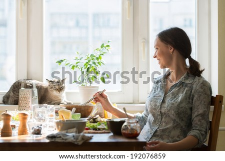 Woman cooking pizza at home. Filling dough with ingredients, while cat relaxing on window - stock photo
