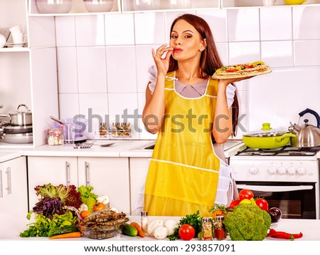 Woman cooking pizza at home white kitchen.