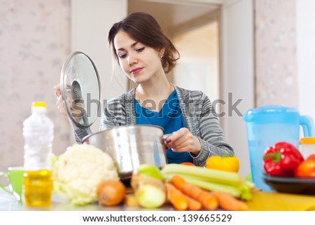 woman cooking vegetarian lunch in  kitchen  at home  - stock photo