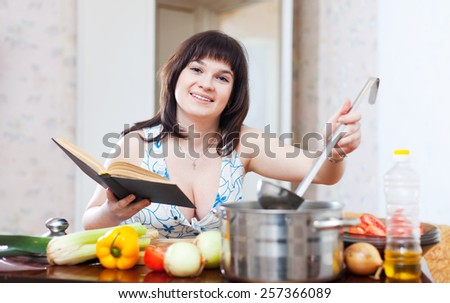 Woman cooking with book and ladle in kitchen