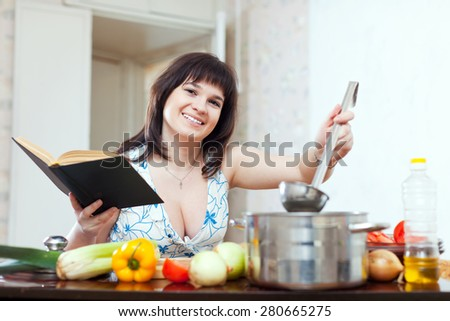 Woman cooking with book in kitchen