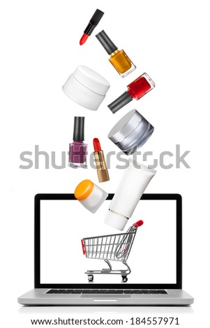 Woman cosmetics falling into notebook isolated on white. Shopping concept - stock photo