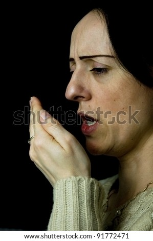 woman coughing, sneezing into hand black background