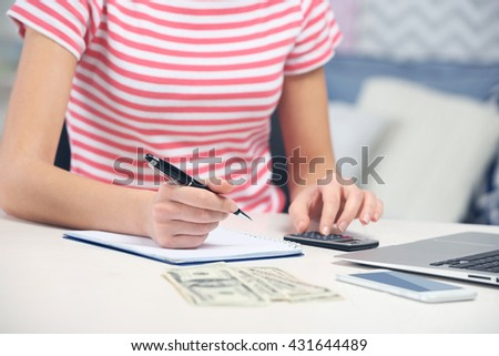 Woman counting money and making calculations - stock photo
