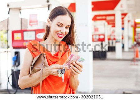 woman counting money on a gas station - stock photo