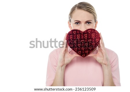 Woman cover her face with heart shaped gift