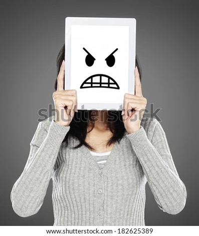 woman cover her face with tablet showing angry emotion icon - stock photo