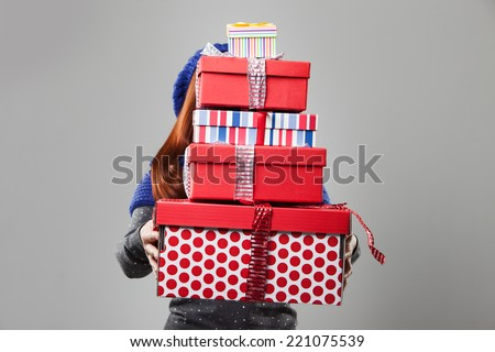 Woman Covered by Carried Gift Boxes Isolated on Gray Background. - stock photo