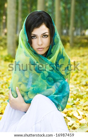 Woman covered by headscarf in a forest. - stock photo
