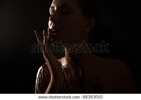 Woman covered in melted chocolate - stock photo