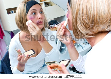 woman covering bruises with make up powder in front of the mirror - stock photo