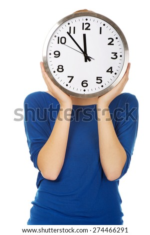 Woman covering face with a clock.