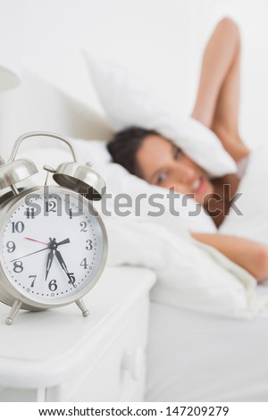Woman covering her ears with pillow while the alarm clock is ringing - stock photo