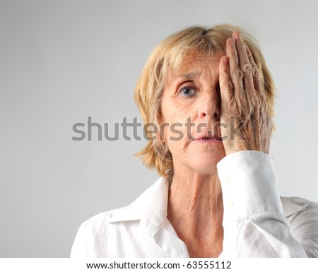 Woman covering her eye with her hand - stock photo