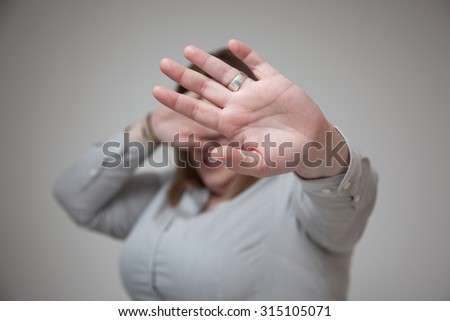 Woman covering her face and saying stop