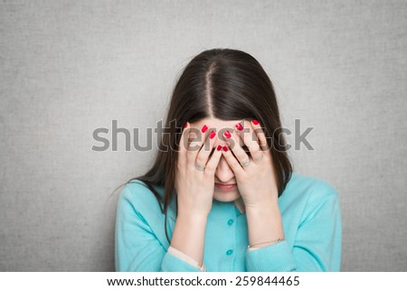Woman covering her face with both hands isolated  - stock photo