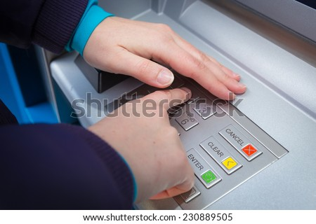 Woman covering her hands whilst entering her PIN at an ATM - stock photo