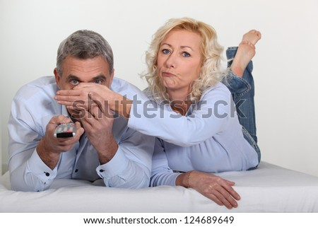 Woman covering her husband's eyes - stock photo