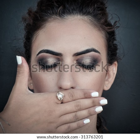 woman covering her mouth with her hand - stock photo
