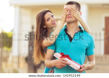 woman covering man's eyes hands. man with gift - stock photo