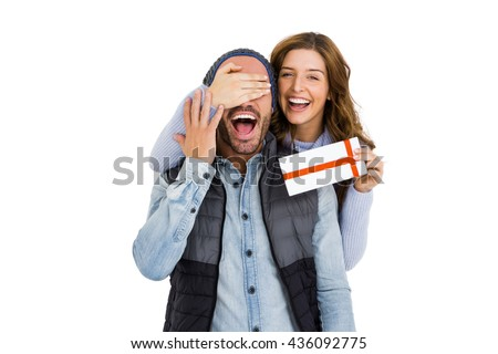 Woman covering mans eyes while giving him a surprise gift on white background - stock photo