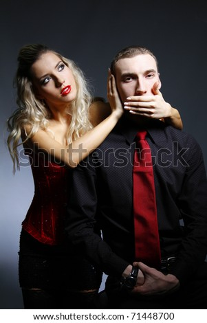 woman covers man's mouth with her hand - stock photo