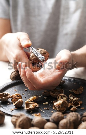 Woman cracking raw shelled almonds