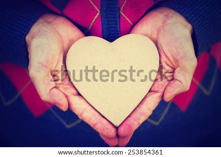 woman craddling a paper heart in the palms of her hands with a retro instagram filter (shallow depth of field) - stock photo