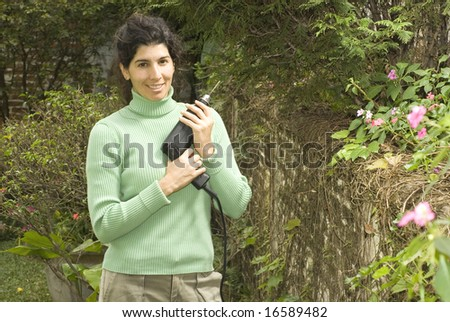 Woman cradles drill against her chest while smiling at the camera. She is standing in a garden. Horizontally framed photo. - stock photo