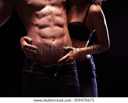 Woman Craving Very Sexy Male Six Pack Abs. Isolated on Black Background - stock photo