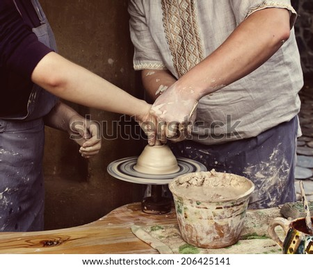 Woman creating a bowl on a Potter's wheel, the master class of pottery art - stock photo
