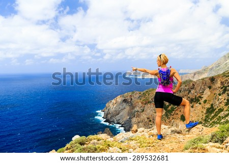 Woman cross country running or hiking, pointing hand at ocean, looking at beautiful inspirational scenic view in mountains and blue sea. Climbing or trail running healthy lifestyle in Crete, Greece - stock photo