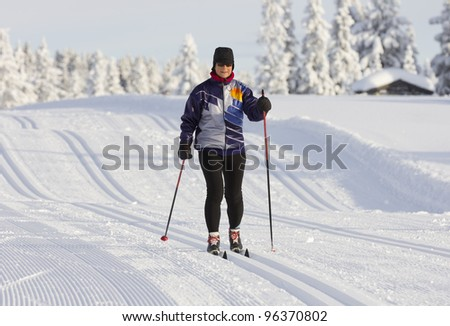 woman cross country skiing on a  sunny winter morning - stock photo