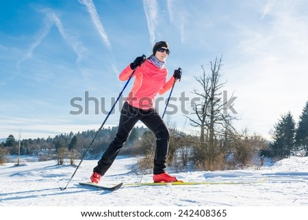 Woman cross country skiing on a yellow skis - stock photo
