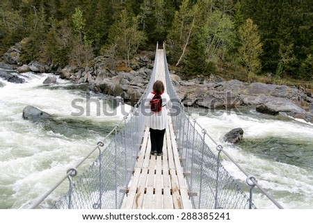 Woman crossing a foaming stream on a suspension bridge