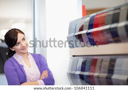 Woman crossing arms while looking at a color palette in a car dealership
