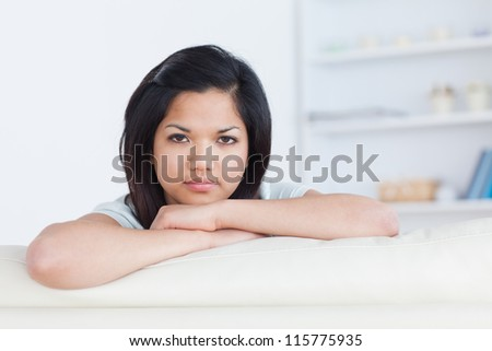 Woman crossing her arms on a white couch in a living room - stock photo