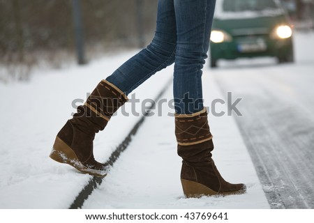woman crossing the snowy road - car in background - stock photo