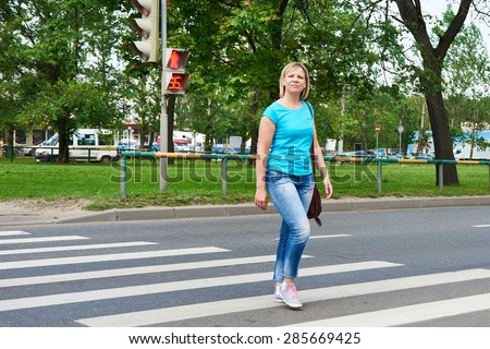 Woman crossing the street is dangerous at a red light - stock photo