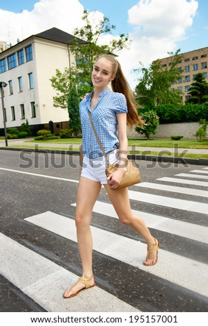 Woman crossing the street on the crosswalk - stock photo