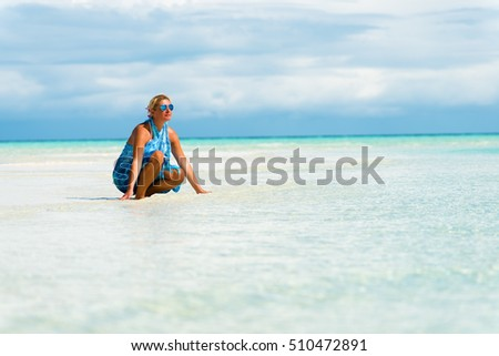 Woman crouched on the white sand beach.Copy space