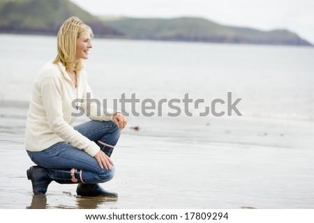 Woman crouching on beach smiling - stock photo