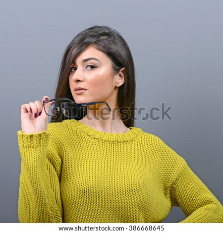 Woman crying and wiping tears against gray background - stock photo