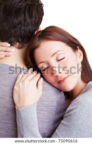 Woman cuddling with her boyfriend while leaning onto his shoulder - stock photo