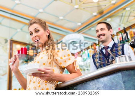 Woman customer in coffee bar drinking cup of cappuccino, in background the barista is preparing a beverage - stock photo