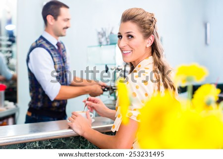 Woman customer ordering espresso or cappuccino at bar counter in coffee shop - stock photo
