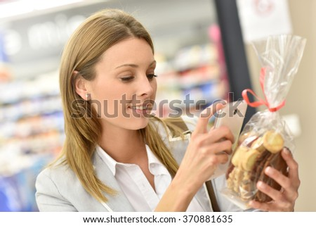 Woman customer scanning food products in grocery store - stock photo