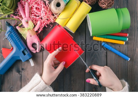 Woman cut red color paper on wooden table - stock photo