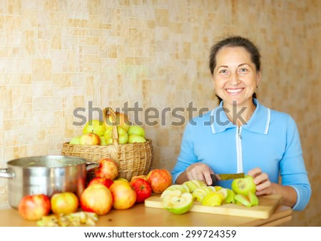 Woman cuts apples for apple jam in kitchen - stock photo